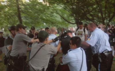 Rangers and Park Police fight to apprehend a protester after National Gathering attendees attempt to erect a tent at another Park Service site near Independence Hall. Photo by Joanne Michele