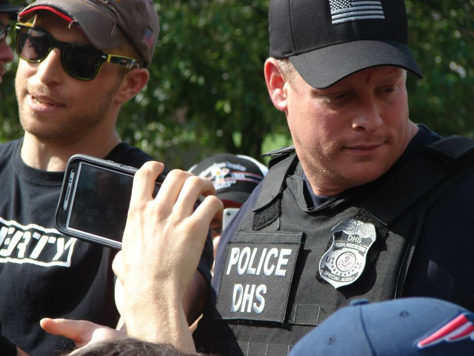 A DHS officer using his smartphone to record Adam Kokesh speaking in the chaotic aftermath of 4:20 at Smokedown 6