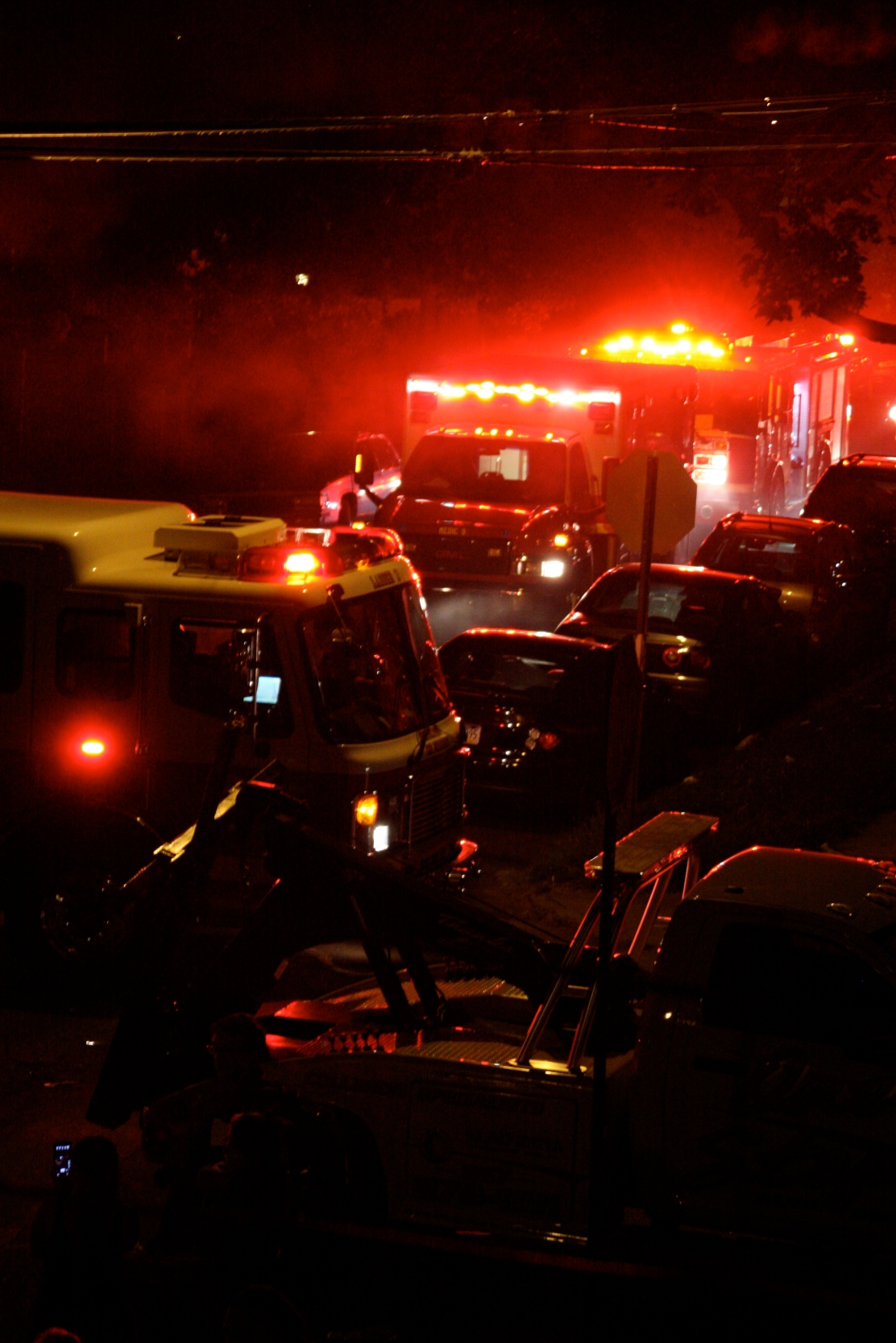 Several firetrucks and ambulances line the street to douse the flames, approximately 15 minutes after the collision. Photo by Kit Friday