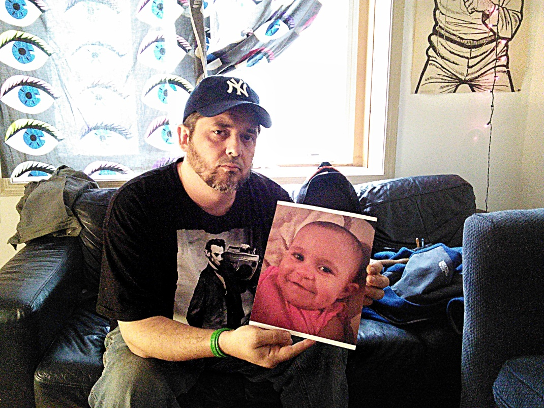 Lefty Grimes with a photo of 15 month old Sabina Rose, who died awaiting implementation of medical marijuana law delayed by Governor Christie