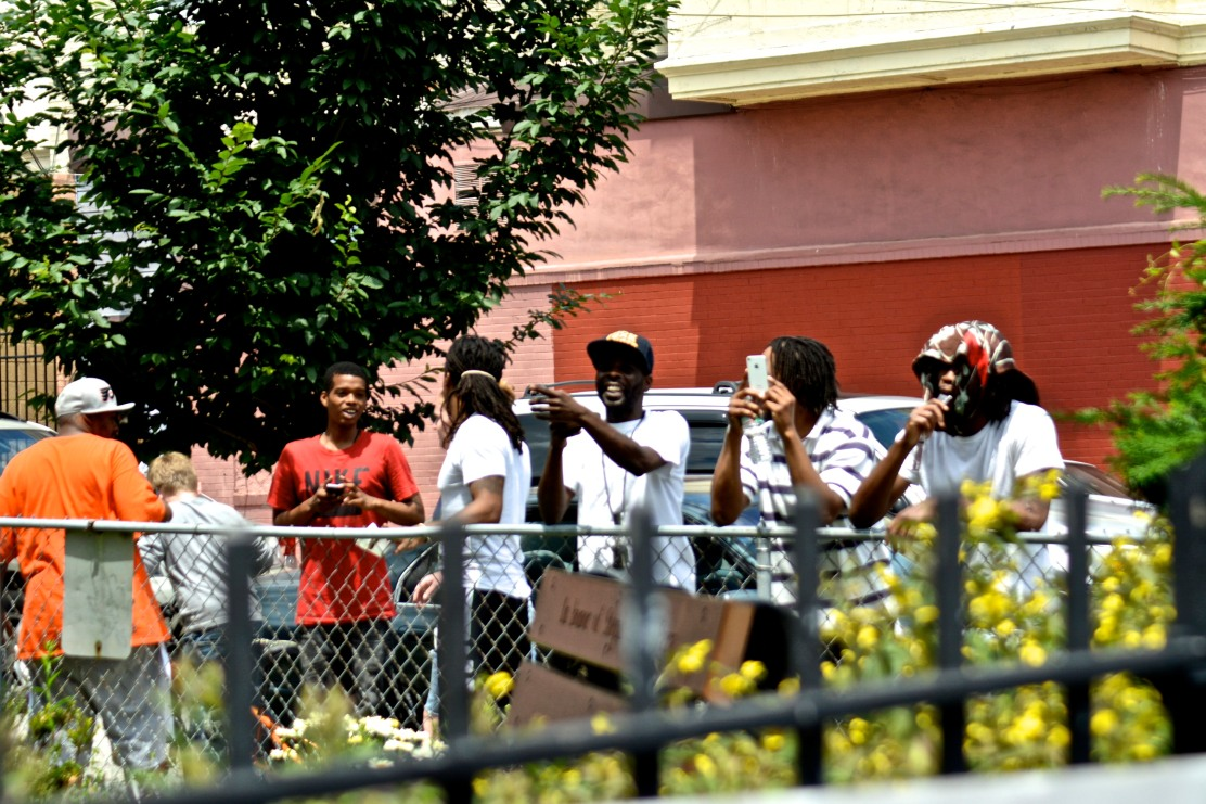 Members of the neighborhood watch and take pictures of the rally. Photo by Joshua Albert
