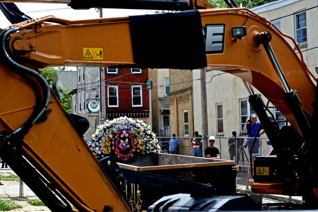 A dumpster, serving as a casket, sits before a crane that will tear down the home at 3711 Melon St.