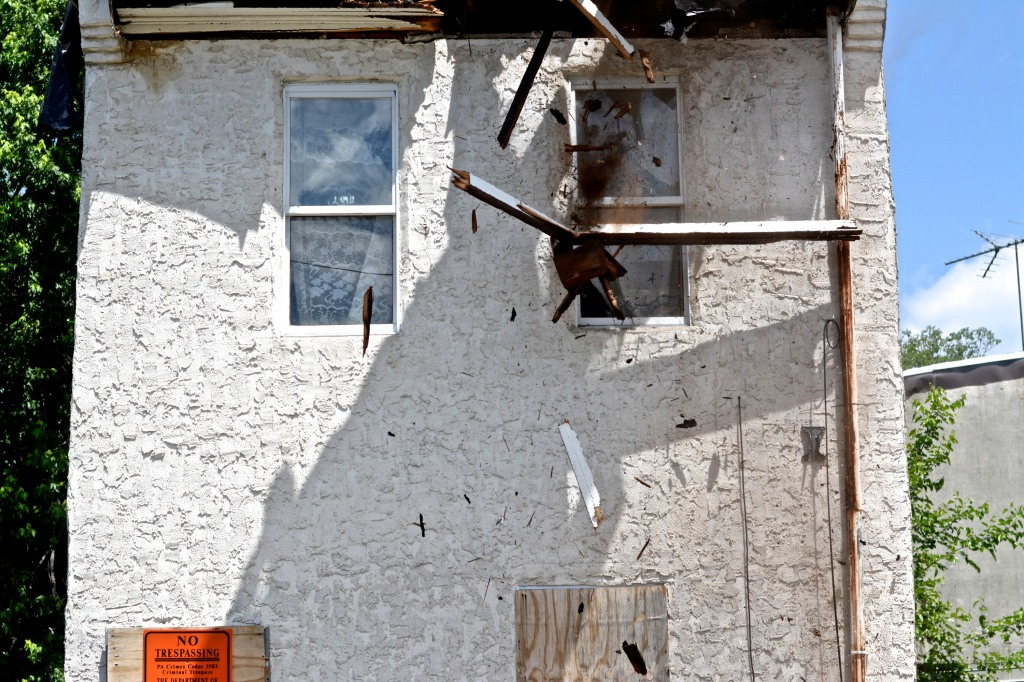 First pieces of debris fall to the ground as the crane begins to tear down 3711 Melon Street.