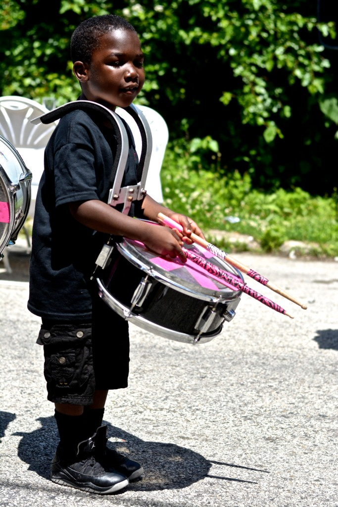 A young drummer prepares to perform as the house is being demolished.