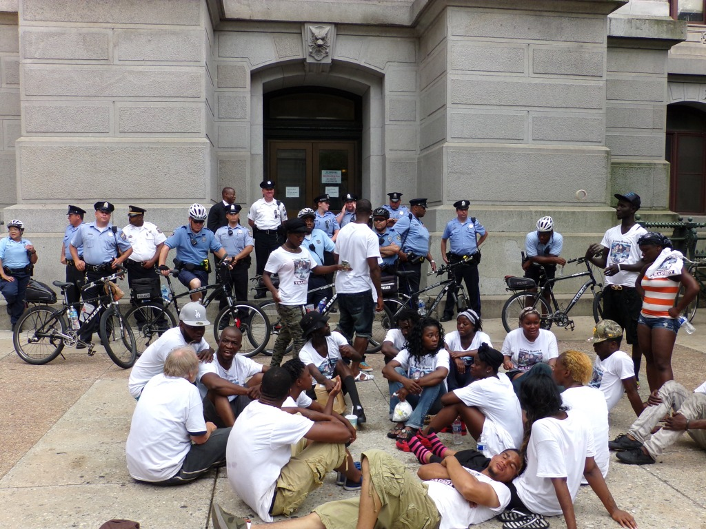 Genser Street residents outside of City Hall on Wednesday afternoon. Patrick Sanyeah, father of the victims, is on the left beneath the man in the gray ball cap. Photo by Kenneth Lipp