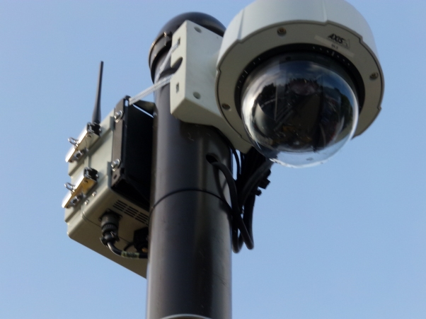 Wireless IP cameras like these allow police to set up ad-hoc surveillance networks without a need for any existing infrastructure. You can see the cameras and routers are recently attached with pipe strap. Photos by Kenneth Lipp.