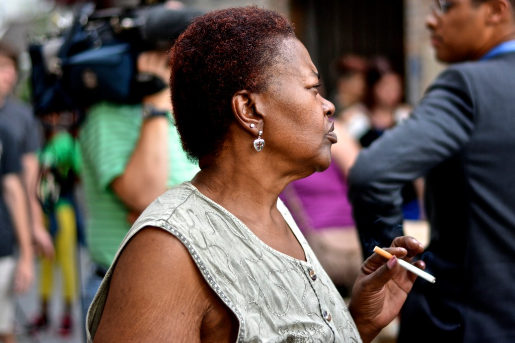 A lady smokes a cigarette while listening to speaker.