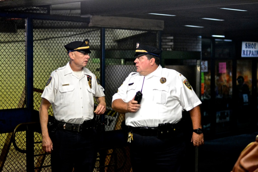 Two SEPTA officer discuss and watch protesters. ( Photo By Joshua Albert)