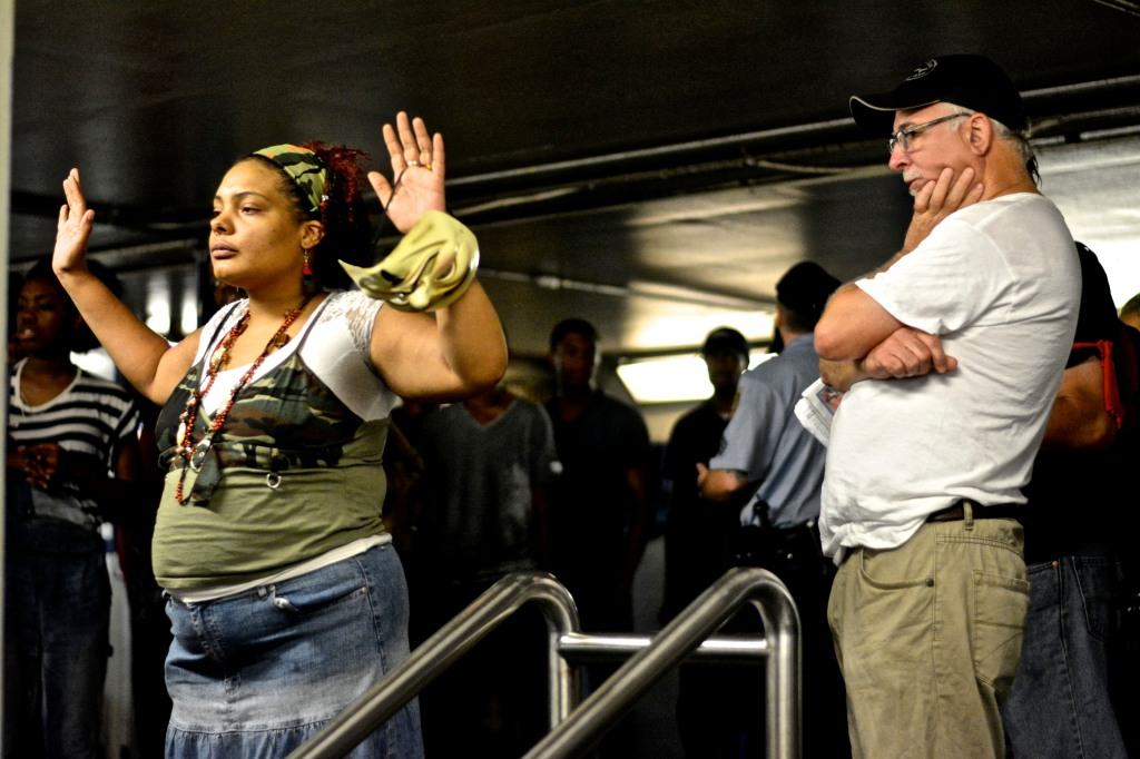 A protester holds her hands up to signify she is unarmed. ( Photo By Joshua Albert)