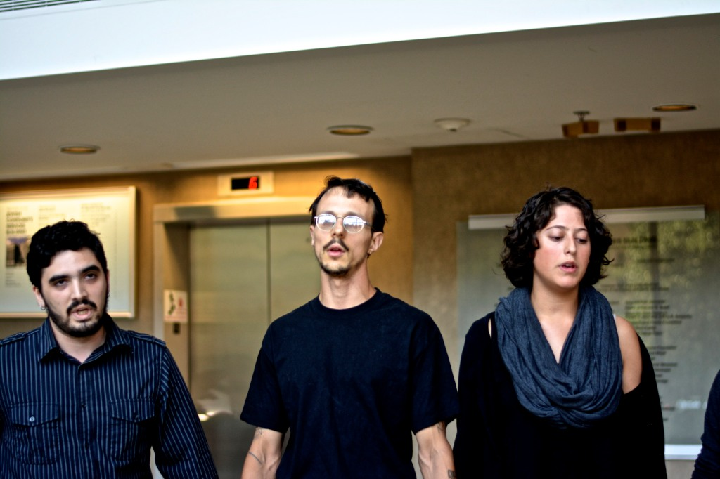 Three of six Jewish Voices for Peace activists hold hands while occupying the Jewish Community Services lobby. (Photo: Joshua Albert)