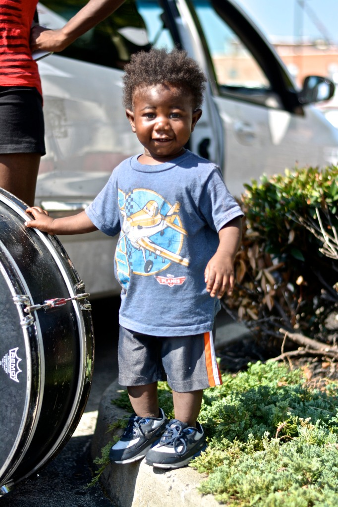 A young child arrives with drum line.