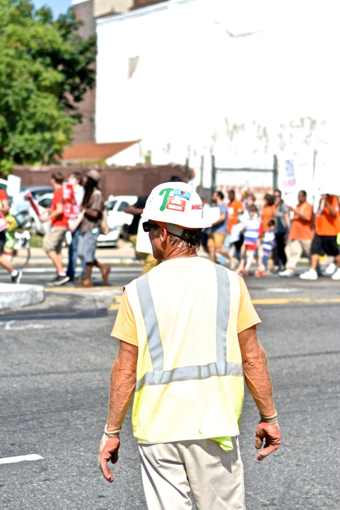 A construction worker pauses to watch march.