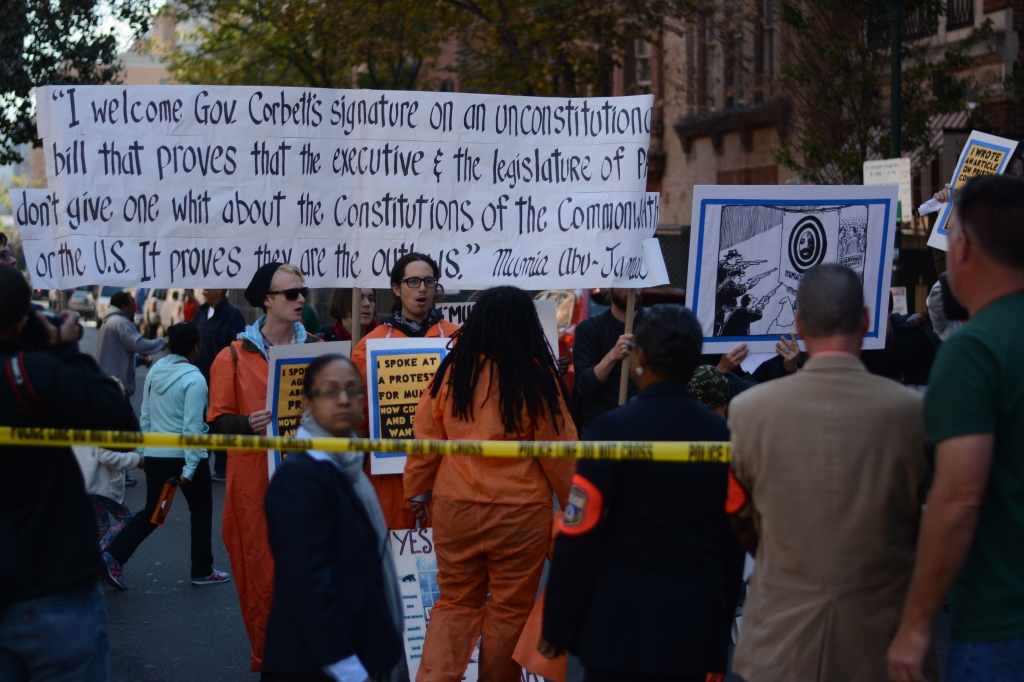 Protesters hold up a banner with Mumia Abu-Jamal's response to the Act's signing. Photo by Joshua Albert