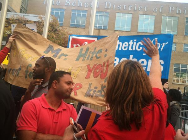 PFT members raise their banner in front of hired anti-union demonstrators. Photo: Regina Medina/Philly Daily News