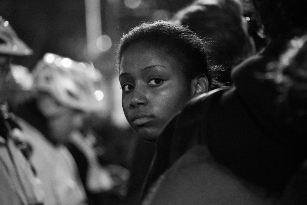 A young woman stands with dozens of protesters outside the 9th District police station Tuesday night.