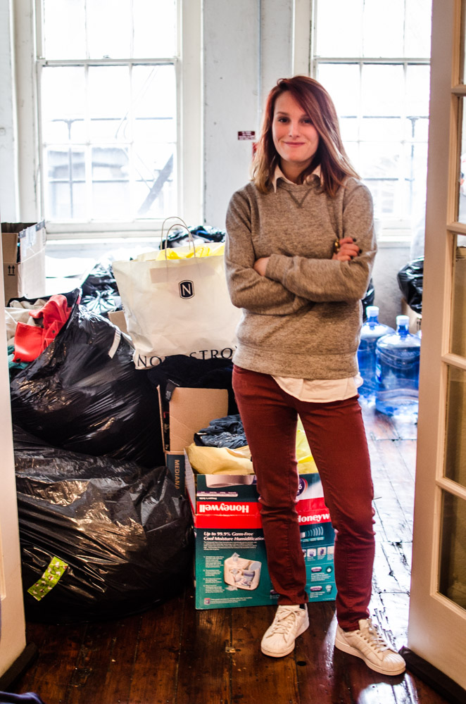 Jessica Smith stands in her office with a portion of the clothes donated.