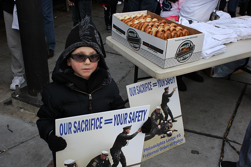 A young police supporter holds a sign at the corner of Oregon Avenue and Broad Street. Photo by Kenneth Lipp